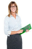 Bespectacled entrepreneur holding calculator. Pretty corporate female pressing number three on a large green calculator stock illustration