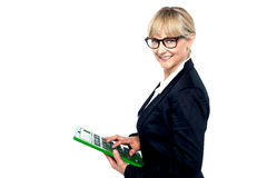 Bespectacled entrepreneur using a calculator. While smiling at the camera stock illustration