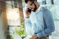 Bespectacled handsome man having phone conversation and using the laptop. Pleasant conversation. Bespectacled happy handsome man sitting in the room having Stock Photography