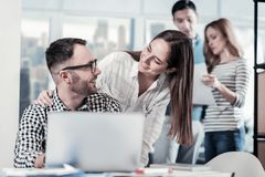 Bespectacled joyful man looking at the colleague and smiling. Well done. Bespectacled joyful unshaken men sitting in the office opposite laptop looking at the Stock Images