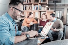 Bespectacled joyful man sitting and working with his laptop. Interesting program. Bespectacled joyful unshaken men sitting in the office on the sofa near his Stock Photography