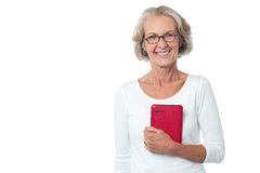 Bespectacled lady posing with tablet pc. Pretty aged lady holding red color tablet device Stock Image