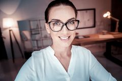 Bespectacled pleasant woman smiling and looking straight. Look at me. Bespectacled pleasant cute woman spending time in the office smiling and looking straight Stock Images