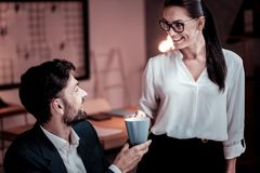 Bespectacled satisfied woman smiling and bringing tea. Take it please. Bespectacled satisfied cute women standing in the cabinet smiling and bringing tea for Royalty Free Stock Images