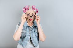 Bespectacled senior woman touching her glasses. Home style. Pretty senior happy woman using headphones and touching glasses while standing against  gray Royalty Free Stock Photography