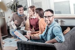 Bespectacled smiling man holding the tablet and looking straight. My team. Bespectacled handsome smiling men sitting on the sofa near his colleagues holding the Stock Photos