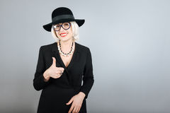 Bespectacled smiling senior woman rising thumb. Lucky you. Happy senior beautiful woman rising thumb and smiling while standing against isolated gray background Royalty Free Stock Photography