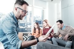Bespectacled thoughtful man holding the document and overlooking it. Interesting facts. Bespectacled thoughtful unshaken men sitting in the room on the chair Royalty Free Stock Photo