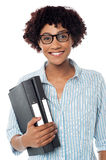 Bespectacled woman in casuals holding files Stock Images