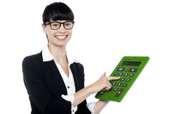Bespectacled woman using big green calculator Stock Photos