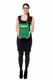 Bespectacled young female displaying calculator. Bespectacled employee displaying big green calculator Royalty Free Stock Photos