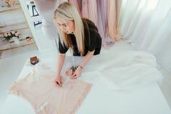 Bespoke service fashion designer women clothing. Bespoke service. Top view of female fashion designer making elegant woman clothing for VIP clients royalty free stock photos