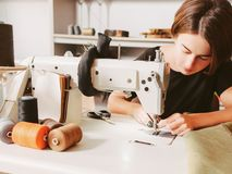 Bespoke service seamstress threading needle. Bespoke service. Tailor workplace. Seamstress sewing clothes and threading needle stock photography