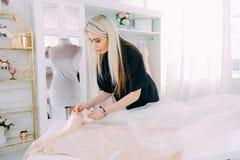 Bespoke service workshop dressmaking business. Bespoke service. Modern workshop. Dressmaking business. Lady working on new dress design for customer royalty free stock images