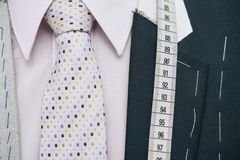 Bespoke suit. Bespoke jacket with necktie and measuring tape stock photography
