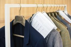 Bespoke tailored jackets hanging on hangers. On a rail with their order information and measurements Stock Image