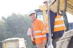Besprechende Aufsichtskräfte beim Gehen an der Baustelle Lizenzfreies Stockfoto