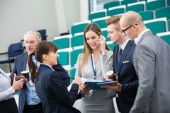 Besprechende Geschäftsleute bei der Stellung in Vorlesungssal stockbilder