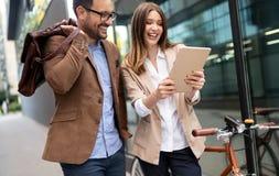 Besprechende und beim im Freien zusammen gehen lächelnde Geschäftsleute stockbilder