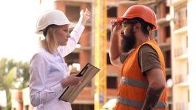 Bespreek vooruitgangsproject De inspecteur en de gebaarde brutale bouwer bespreken bouwvooruitgang Bouwproject stock videobeelden