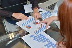 Bespreking van voordelen van businessplannen, bedrijfgrafieken stock foto