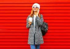 Besprekingen van de manier houdt de gelukkige vrouw op een smartphone koffiekop op een rood royalty-vrije stock afbeelding