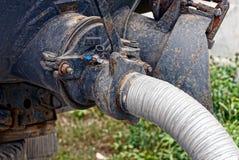 Bespritzen Sie vom Auto im Abwasserkanal auf der Straße mit einem Schlauch Lizenzfreies Stockfoto