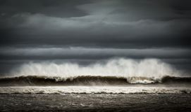 Bespruta att blåsas från stora vågor på en molnig dag royaltyfri bild