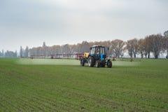 Bespruta för lantgårdtraktor som är agrochemical eller som är agrichemical över ung gr royaltyfria bilder