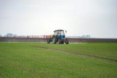 Bespruta för traktor som är agrochemical eller som är agrichemical över ungt korn f arkivbild