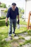 Bespruta växtbekämpningsmedlet på en uteplats Royaltyfri Foto