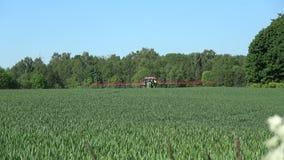 Bespuitend het gewassengebied van de landbouwtractor in de zomertijd stock footage