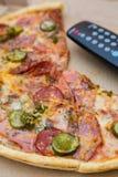 Bessert Pizza im Kasten mit Fernsehfernbedienung aus Lizenzfreie Stockfotografie