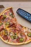Bessert Pizza im Kasten mit Fernsehfernbedienung aus Lizenzfreies Stockfoto