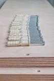 Beställd serie av skruvar och proppar på kryssfaner Arkivbilder