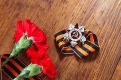 Beställning av den 1st gruppen för patriotiskt krig och två röda nejlikor Stilleben som är hängiven till Victory Day 9 kan Royaltyfri Bild