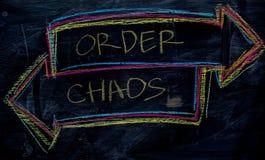 Beställning eller kaos som är skriftliga med färgkritabegrepp på svart tavla royaltyfria foton