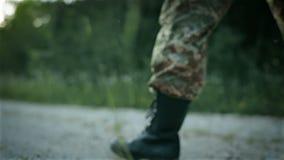 Bestämd militär man som går över den sandiga vägen