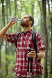 Bestämd ung man som fotvandrar till och med skog, dricksvatten och att vila royaltyfri foto