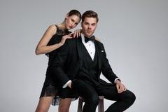 Bestämd ung man som sitter, medan hans flickvän lutar på honom arkivfoton
