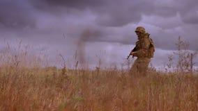 Beständiger starker Soldat, der automatische Waffe hält und Weizenfeld allein in der Tarnung, dunkler bewölkter Himmel während kr stock video