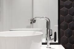 Beståndsdel av badruminre med den vita vasken och den stora spegeln Ny tvättställ och svart sexhörnig tegelplattategelplatta royaltyfri foto