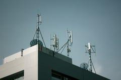 Beståndsdelen av kommunikationsapparater, stora antenner monterade på ett tak Fotografering för Bildbyråer