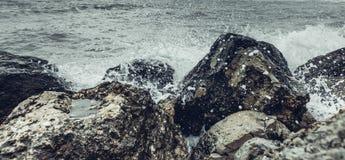 Beståndsdelstyrkabegrepp Vågor som bryter på kusten med havsskum, närbild Naturloppaffärsföretaget stenar havet arkivfoton
