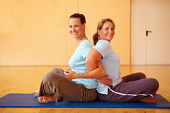 Best Ager doing back exercises. Two happy Best Ager doing back exercises in gym Stock Photos