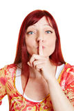 Woman putting finger on her lips. Best ager woman putting index finger on her lips Royalty Free Stock Photos