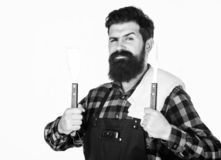 Best barbecue cookware. Bearded man holding barbecue tools in hands. Grill cook using spatula and barbecue fork. Happy. Hipster holding stainless steel tools royalty free stock images