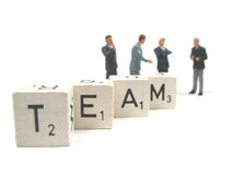 Only the best belong in this businessteam. A couple of businessmen in the background of the word team stock photography
