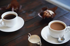 The best breakfast on the go. Two cups of plain coffee with muffins beside them on a dark wood table Royalty Free Stock Photography