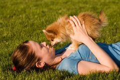 Best Buddies. Attractive teen holding her adorable Pomeranian puppy as she lays on a grassy lawn. They are looking into each other's eyes royalty free stock photo